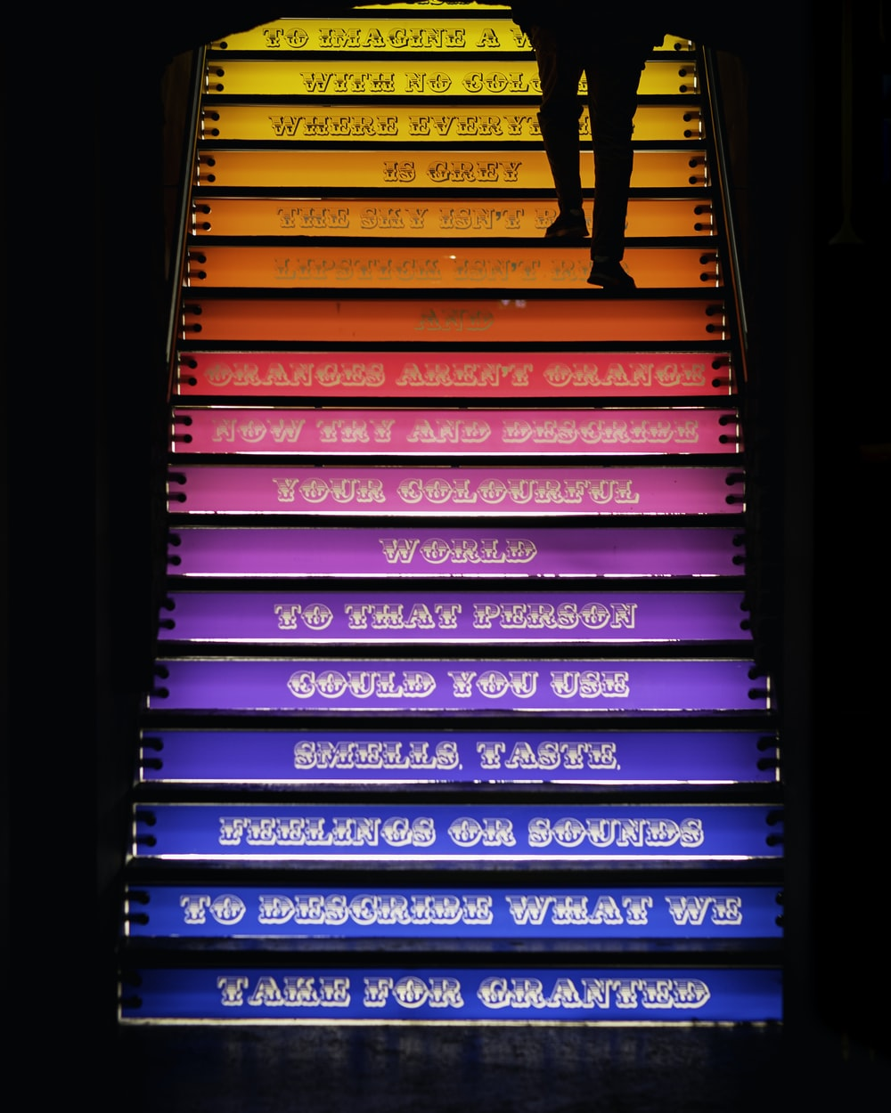 person walking through stairs with assorted-color steps