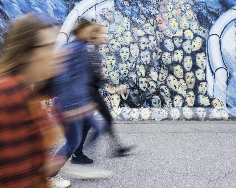 time lapse photography of three person walking beside graffiti wall