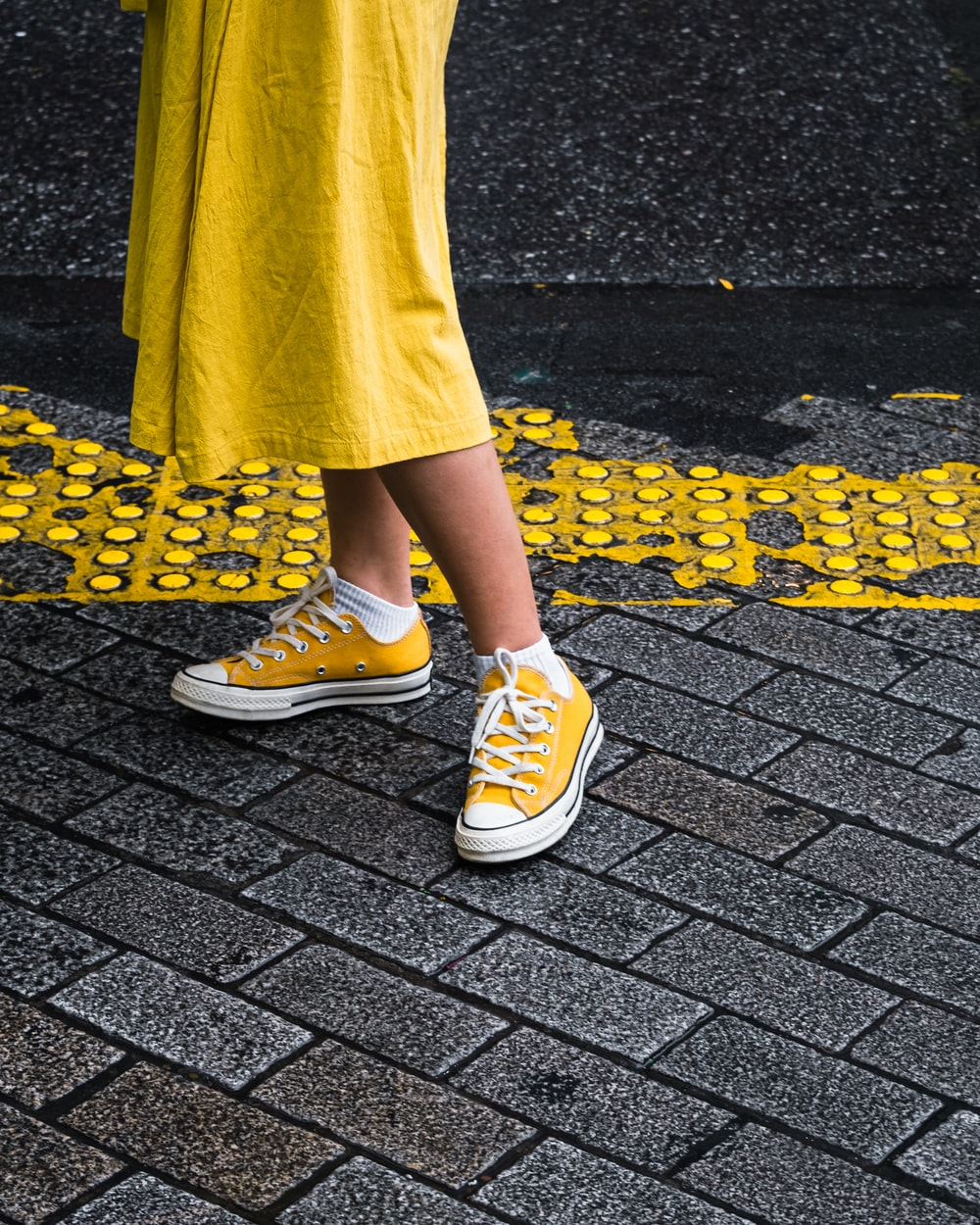 person wearing yellow maxi dress and yellow Converse low-top sneaker