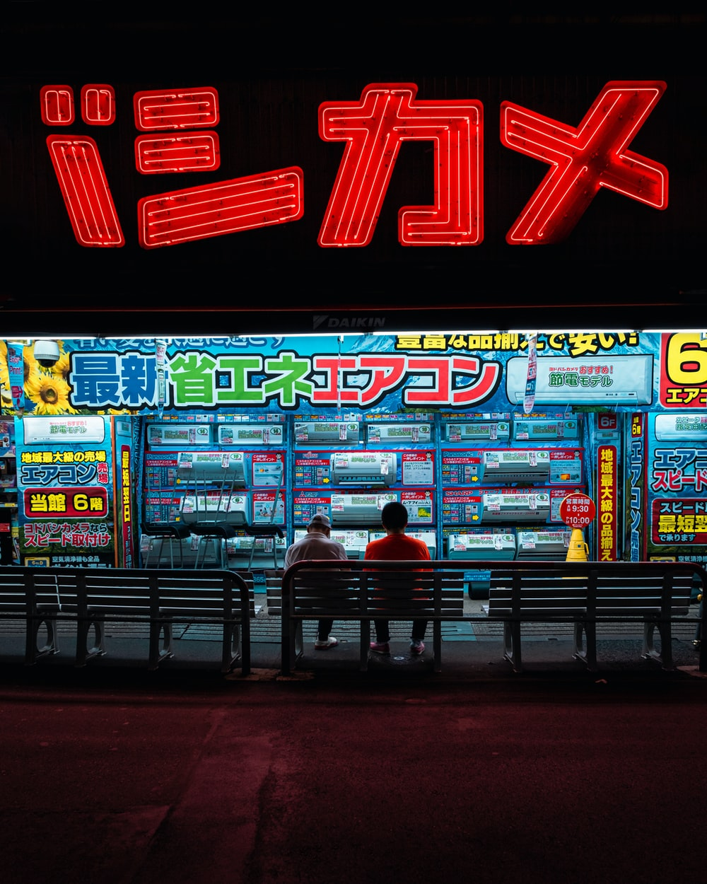 two person sitting on bench in front of store