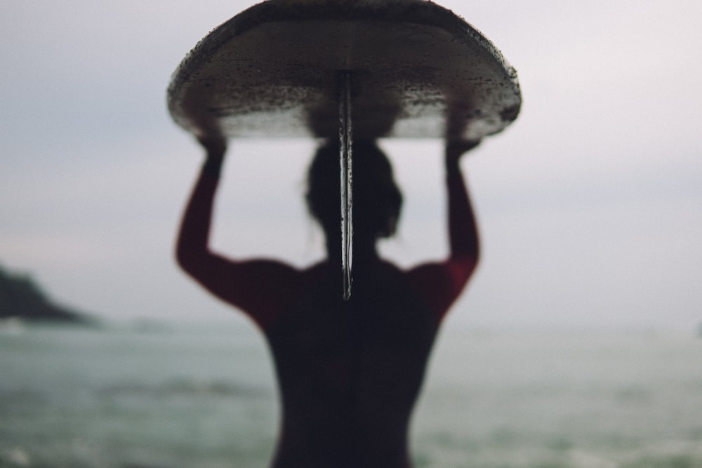 silhouette photography of woman carrying surfboard
