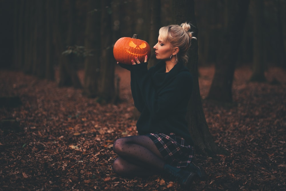 woman in black sweater holding pumpkin