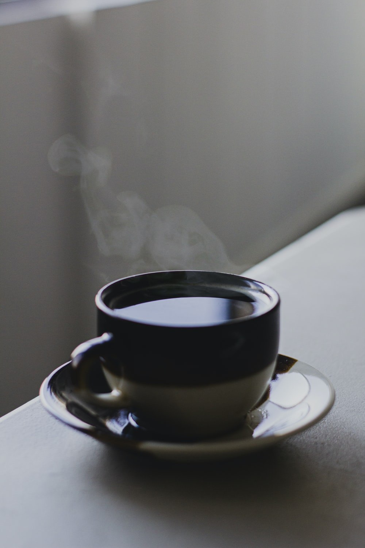 black ceramic mug with brown and white ceramic saucer
