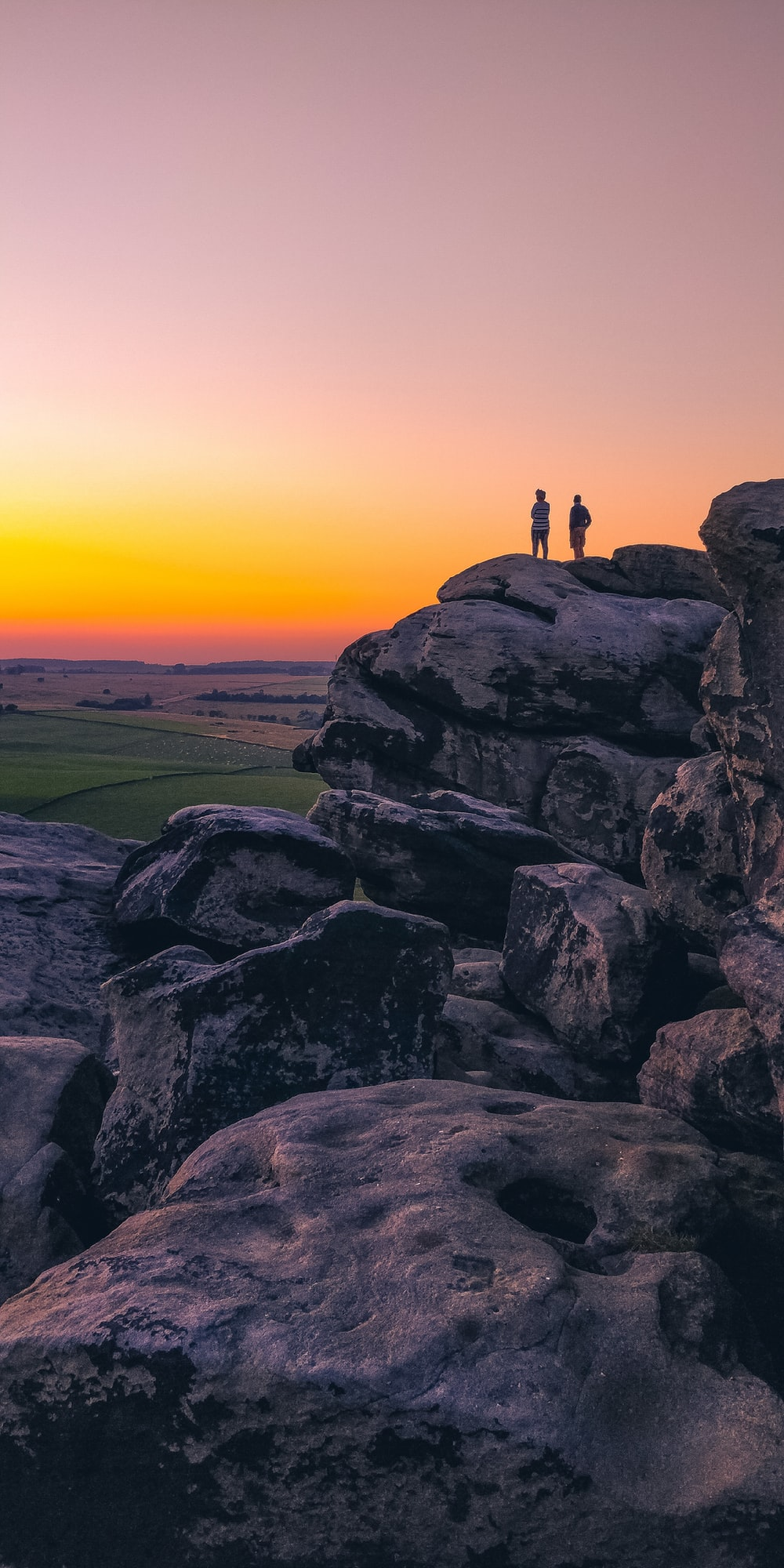 two person standing on cliff