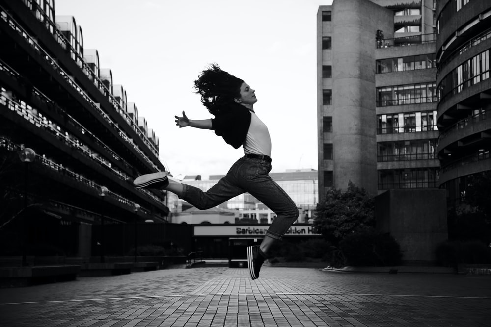 woman jumps on grayscale photography