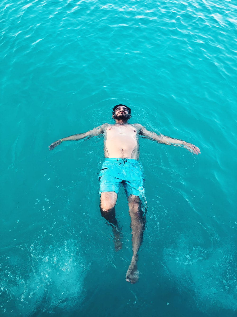 topless man swimming on body of water during daytime