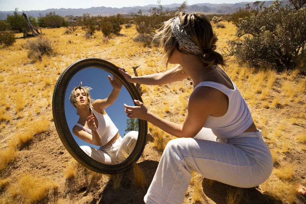 woman in white with a mirror