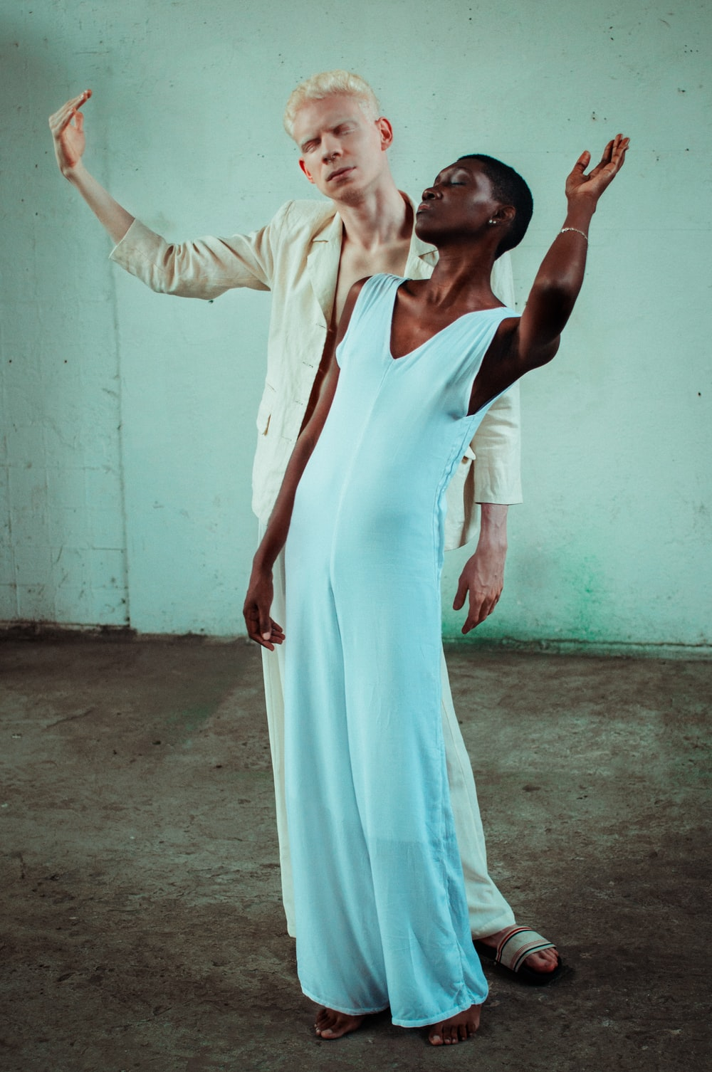 woman in white sleeveless dress behind man in beige dress shirt