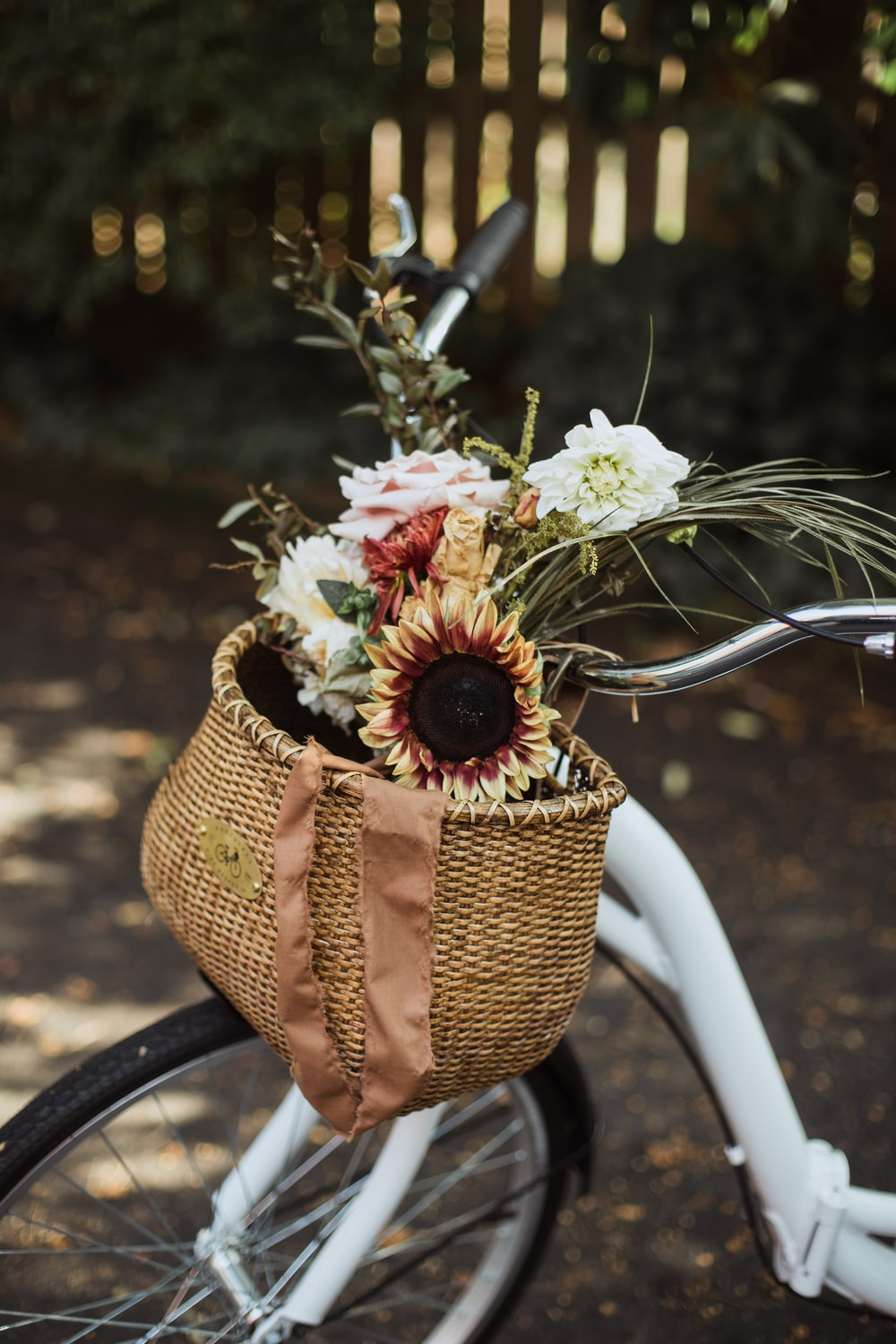 assorted flowers on a brown bike basket