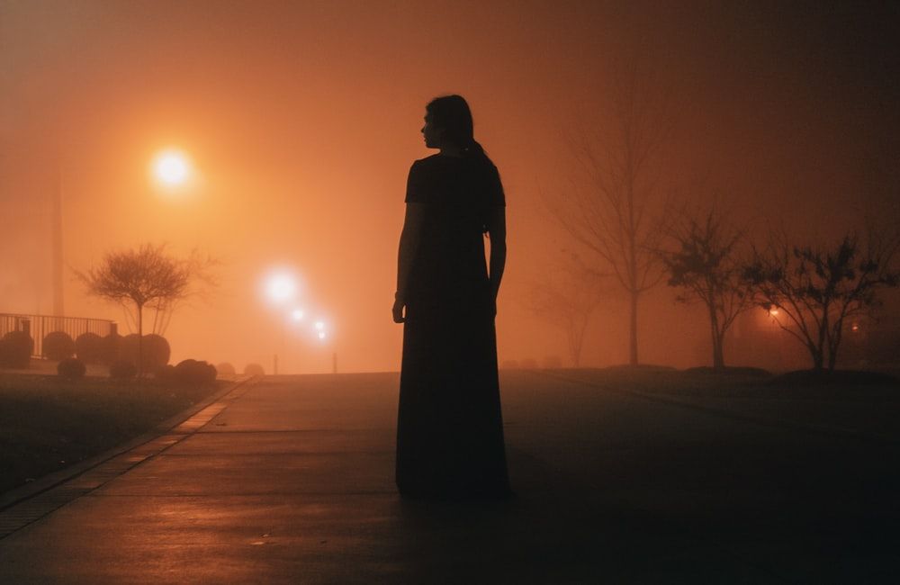 silhouette of woman standing on roadway
