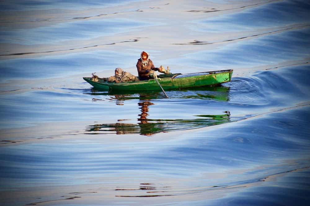 person riding green boat