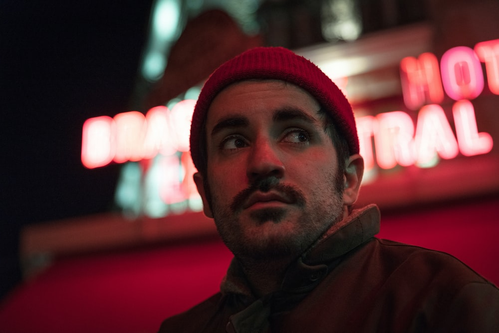 man beside a red neon sign
