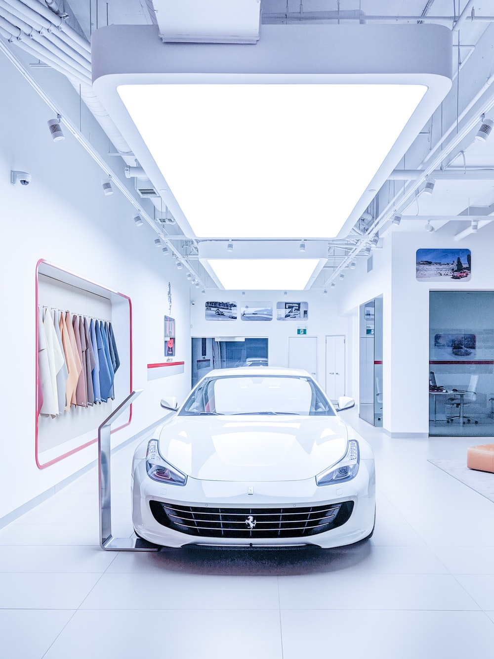 white Ferrari inside white building with hanged clothes