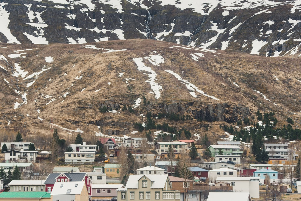 aerial photography of buildings beside mountain