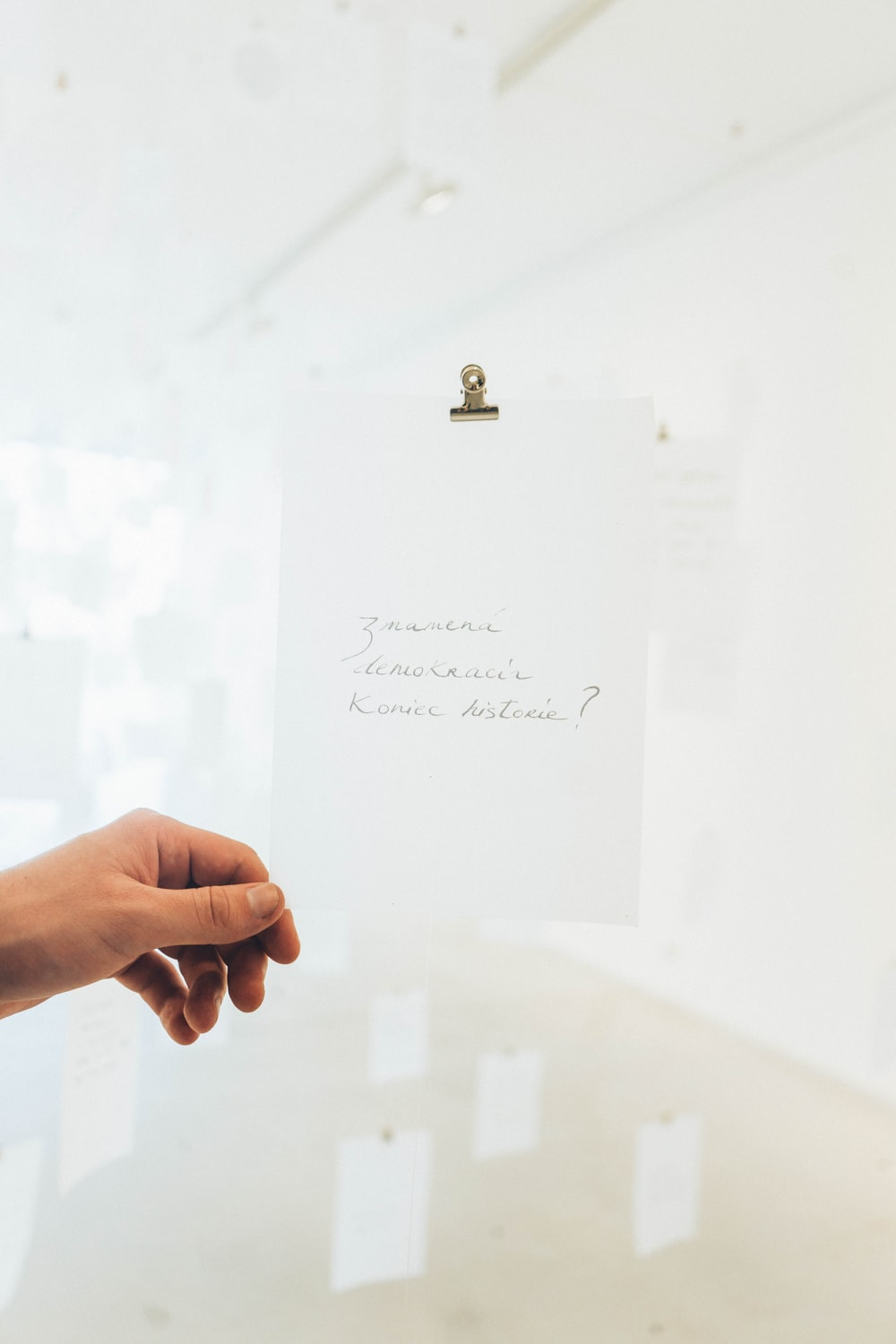 white printer paper with clip holding person's left hand