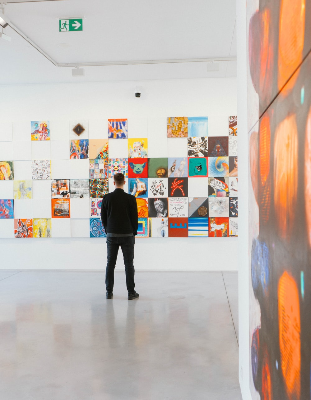 man in black long-sleeved shirt and black bottoms standing behind abstract paintings