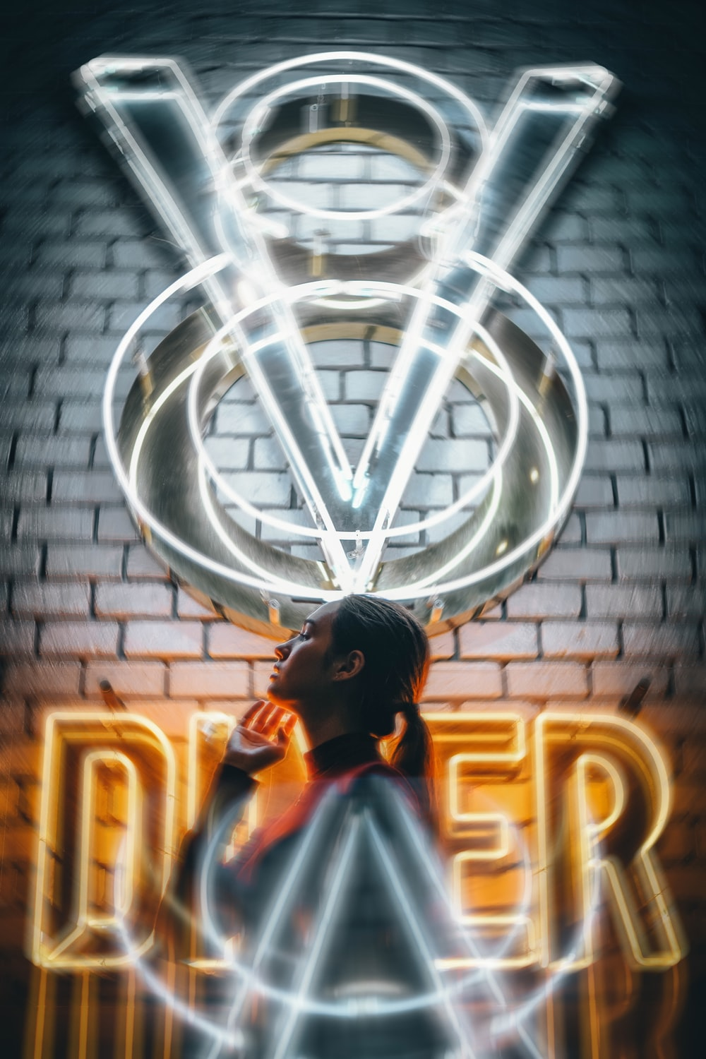 woman standing in front V8 Diner neon sign