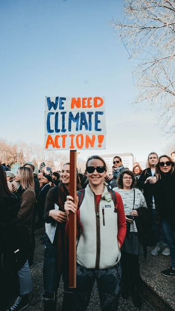 standing and smiling woman holding We Need Climate Action! sign