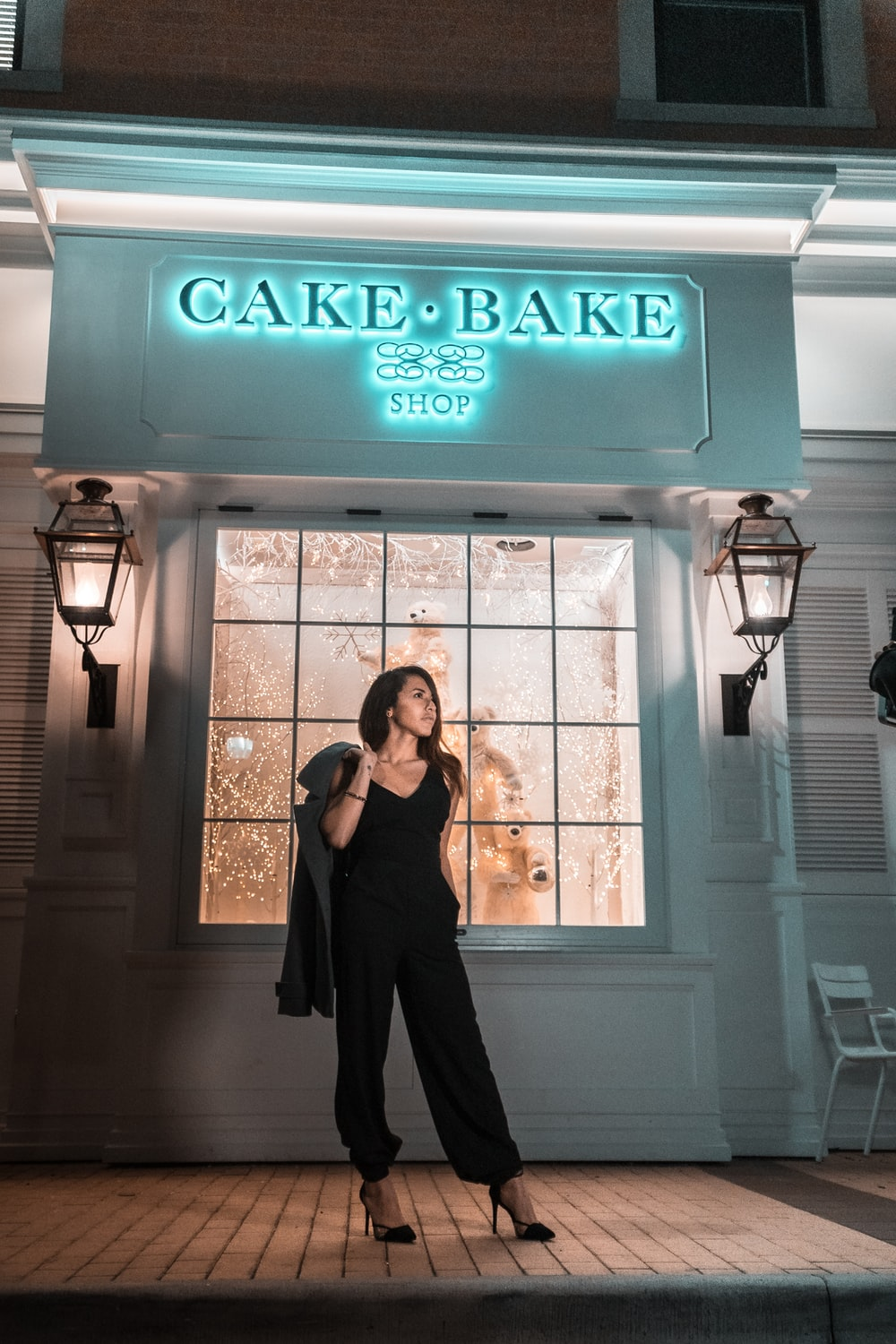 woman standing in front of Cake Bake Shop at night