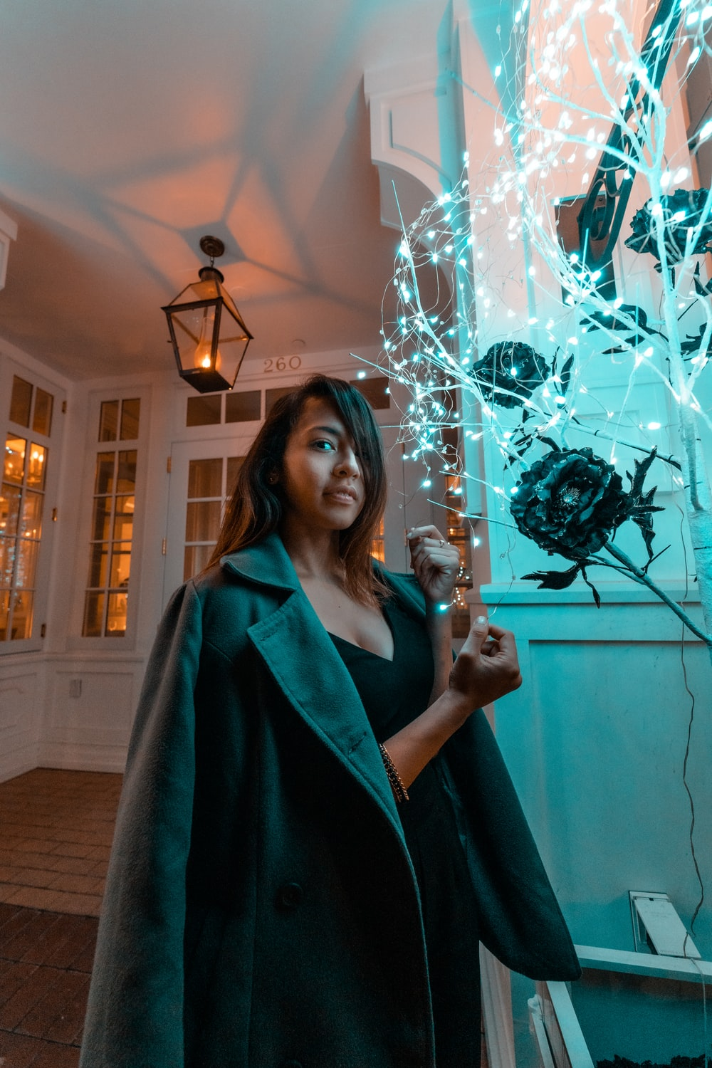 woman standing near lighted string lights