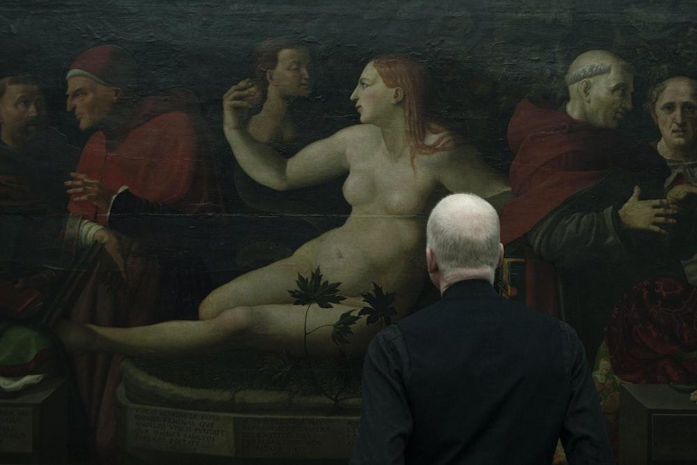 man standing near painting
