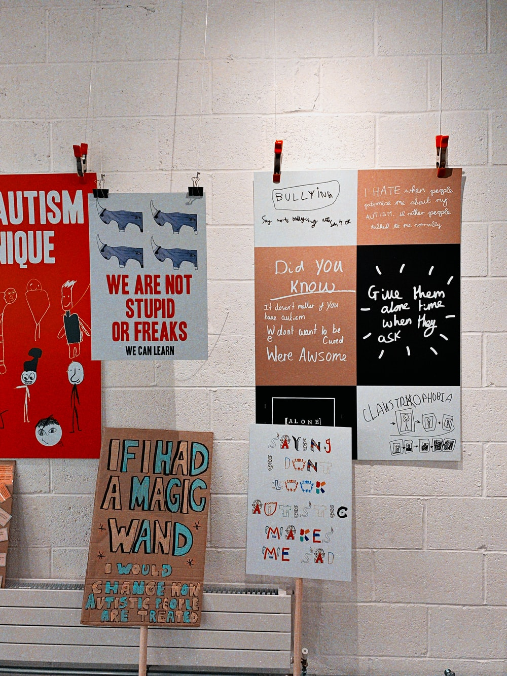 greetings cards hanged by a thread near white brick wall paint