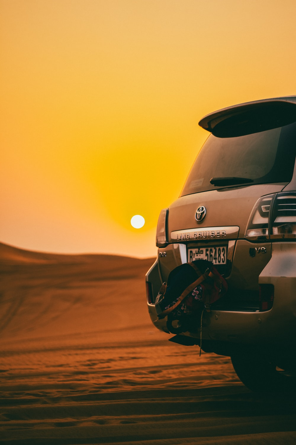 black Toyota Land Cruiser SUV on desert during golden hour