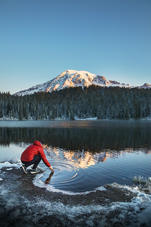 man sitting near body of water