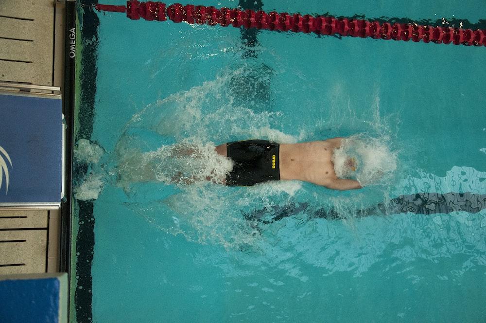 man swimming on swimming pool