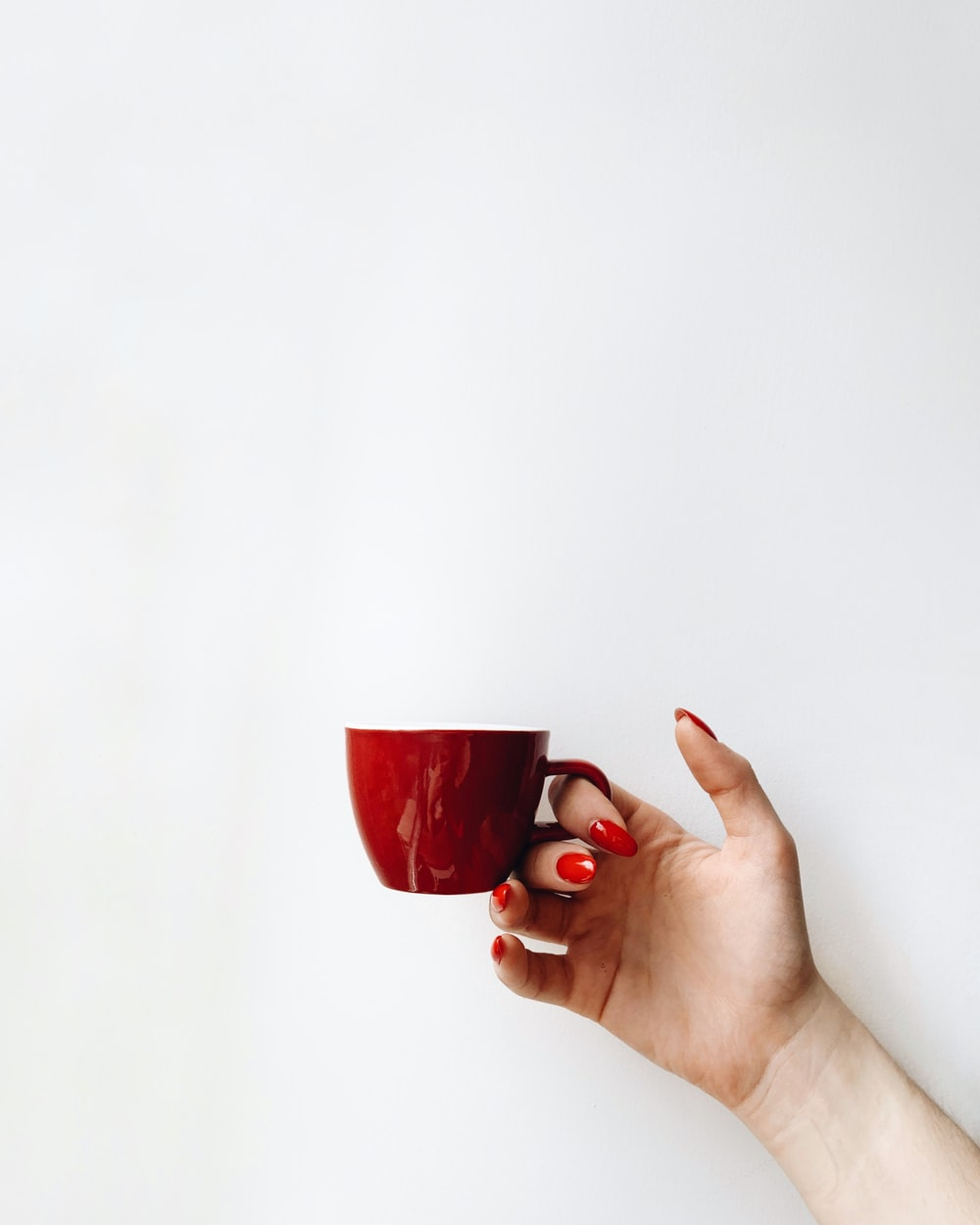 woman with red manicure holds red cup