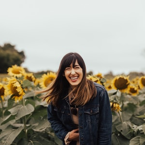 smiling woman standing beside sunflowers