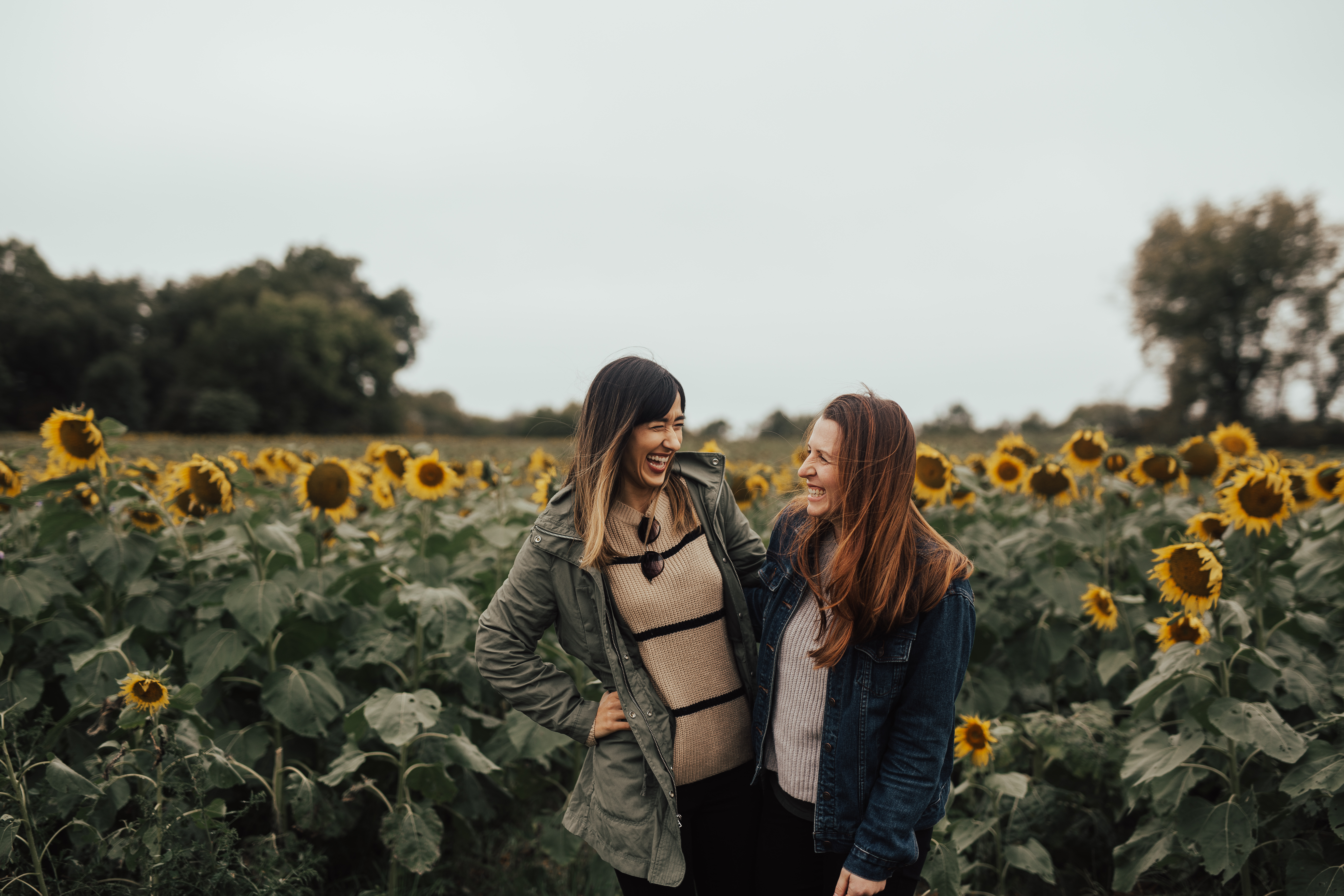 two women standing in front of sunflower field