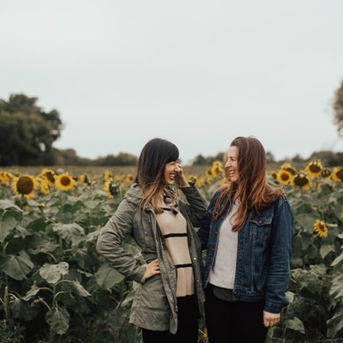 two women near yellow sunflowers