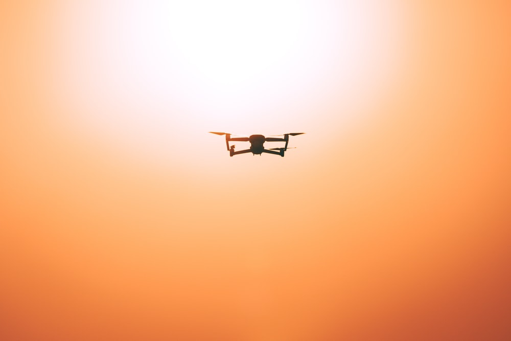 white drone flying during sunset