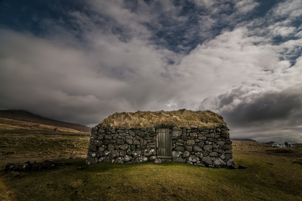 stone house on hill under blue cloudy sky