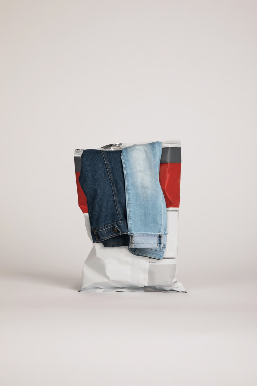 two blue and gray denim jeans on white plastic bag