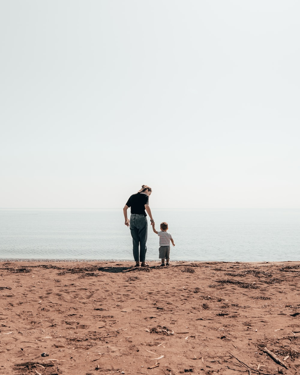 woman and toddler standing beside seashore during daytime