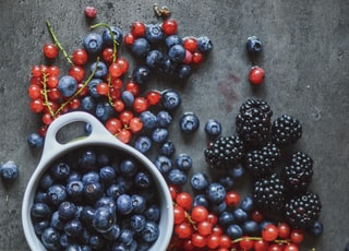 round red and blue berries beside bowl