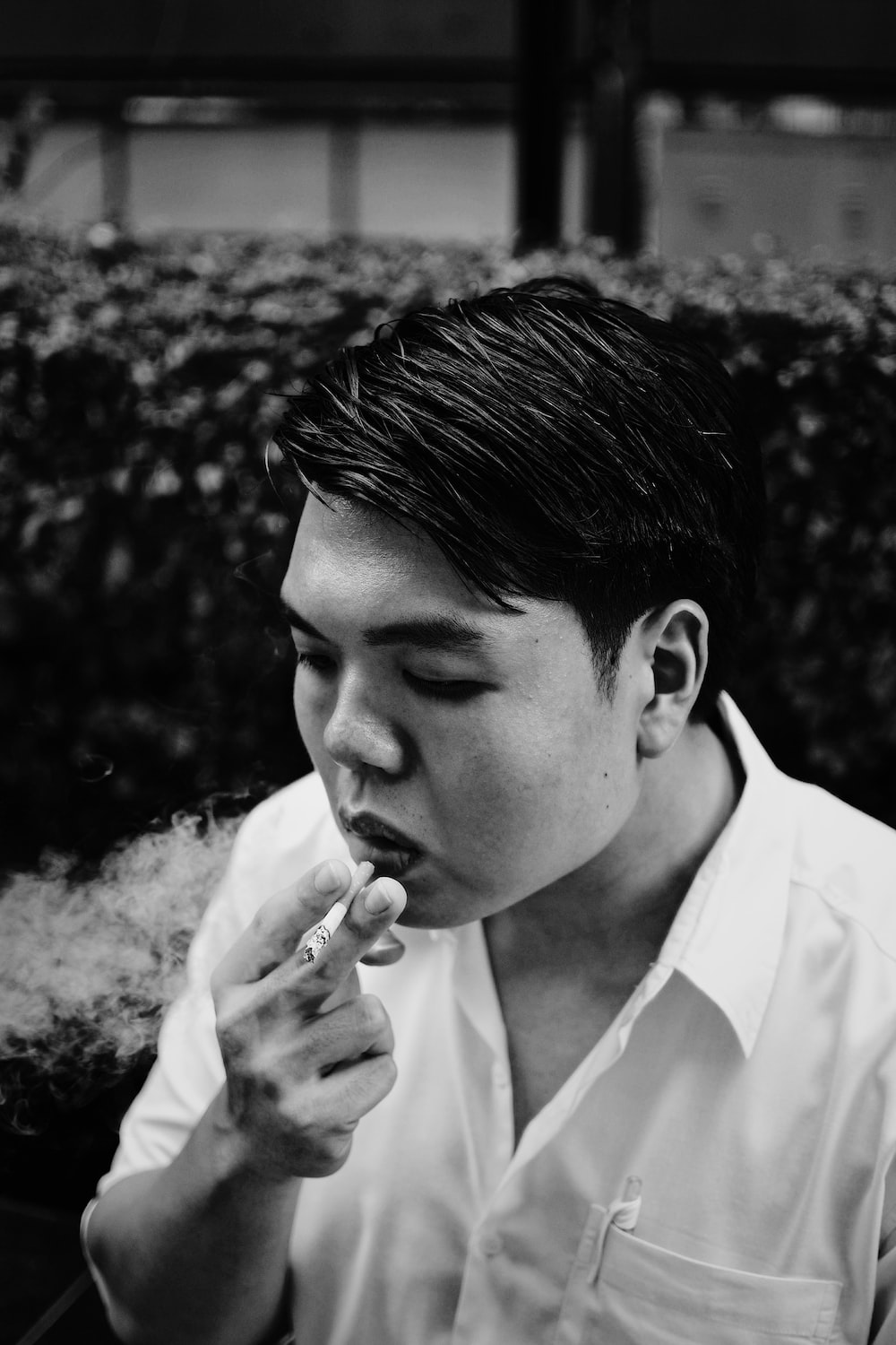 grayscale photography of man smoking beside plant