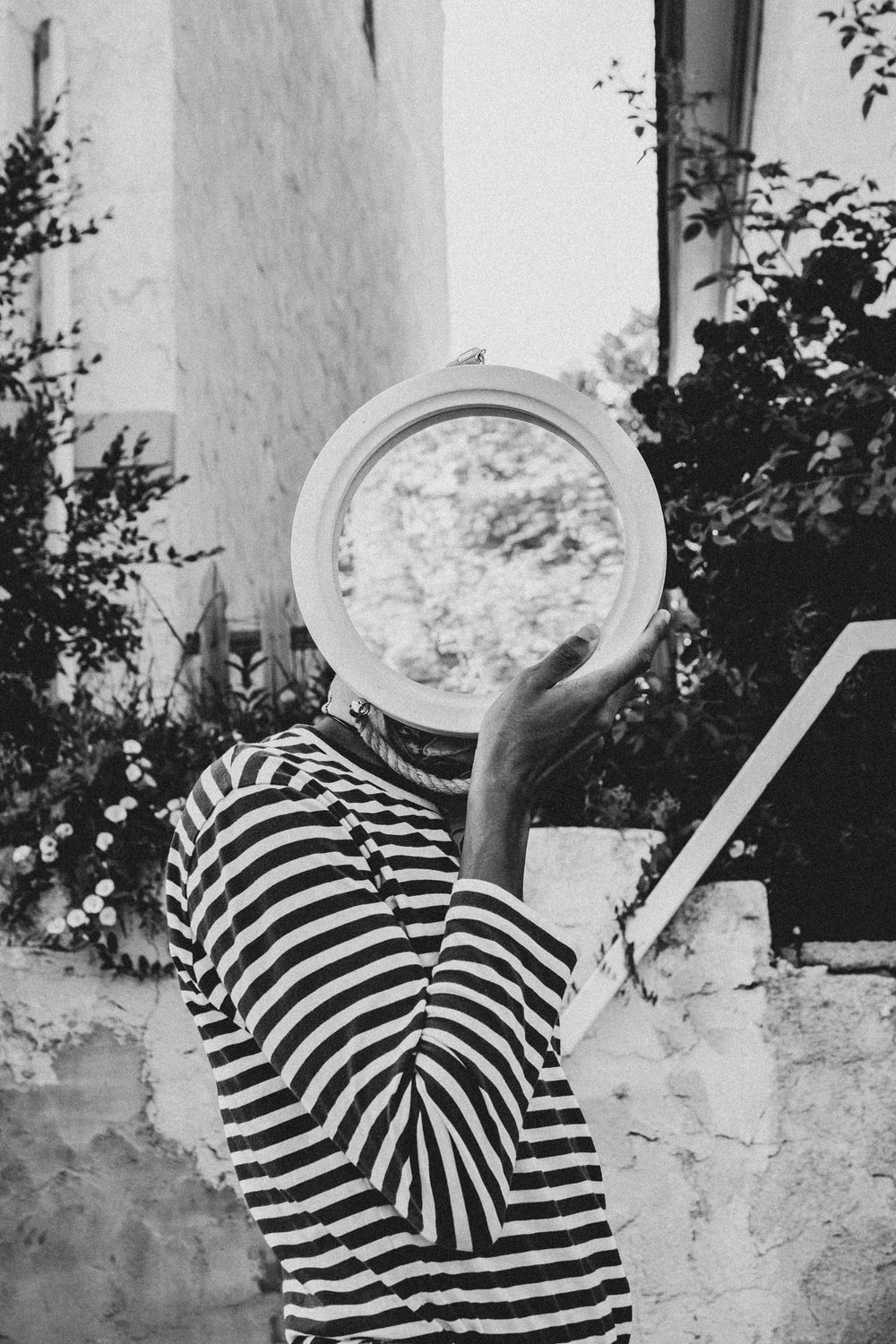 greyscale photography of person holding round decor