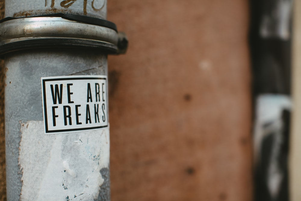 white and black we are freaks sticker
