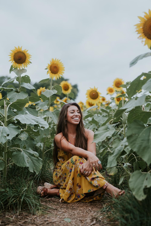 woman sitting beside sunflower during daytime