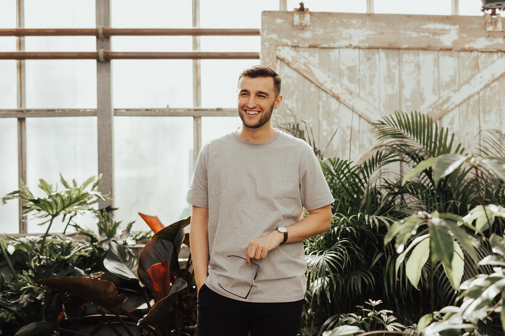 man in grey crew-neck top holding sunglasses standing near plants