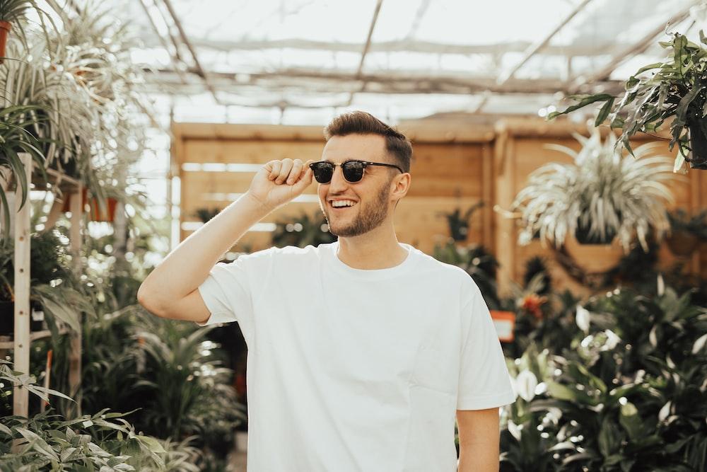 man in white crew-neck shirt wearing sunglasses standing near plants