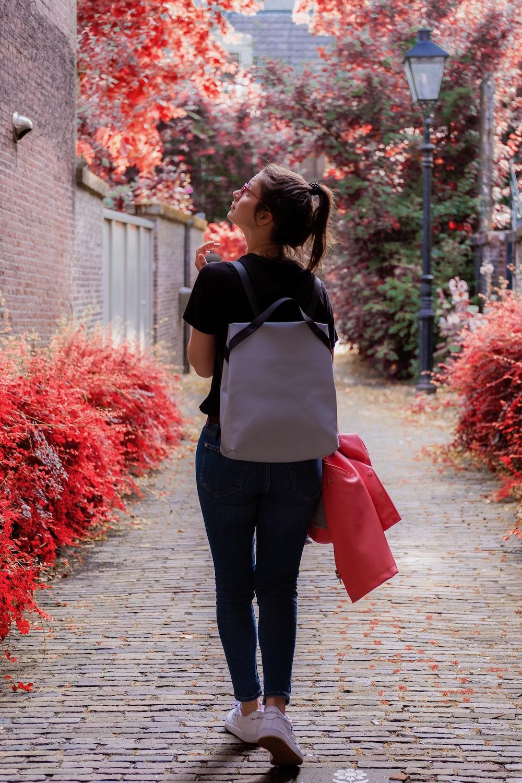 woman wearing black shirt and leggings carrying backpack