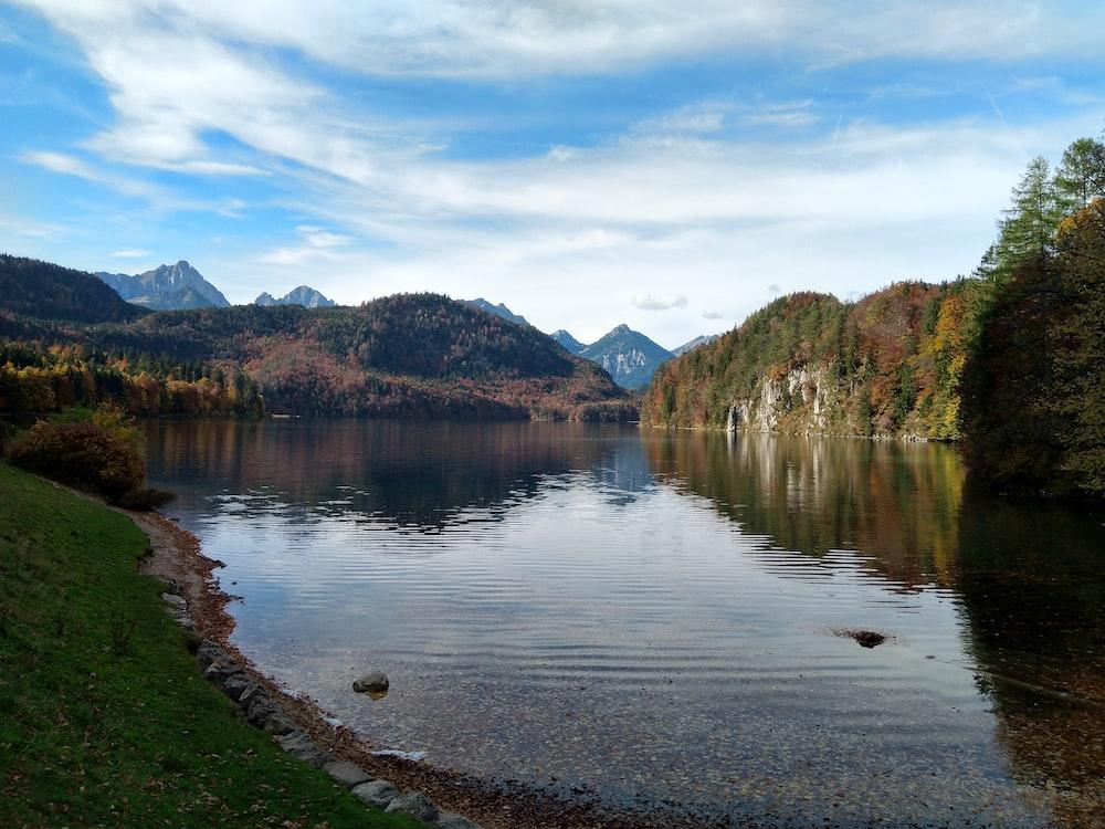 lake near hills at daytime