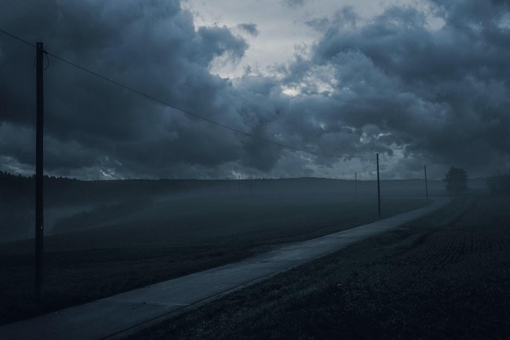 roadway beside street post under cloudy sky