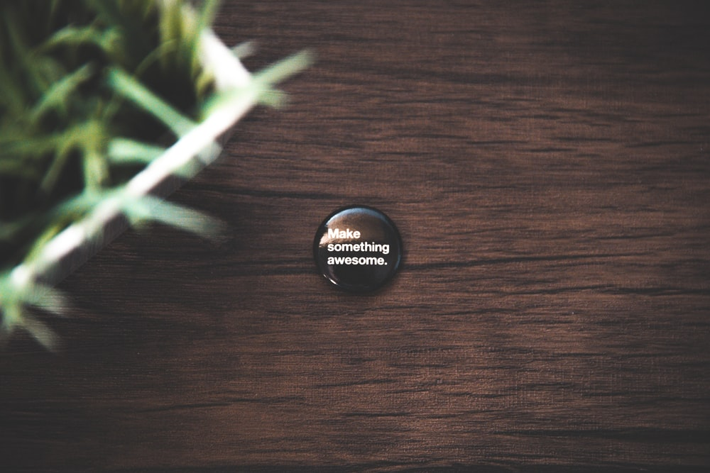 round black button pin on brown wooden surface