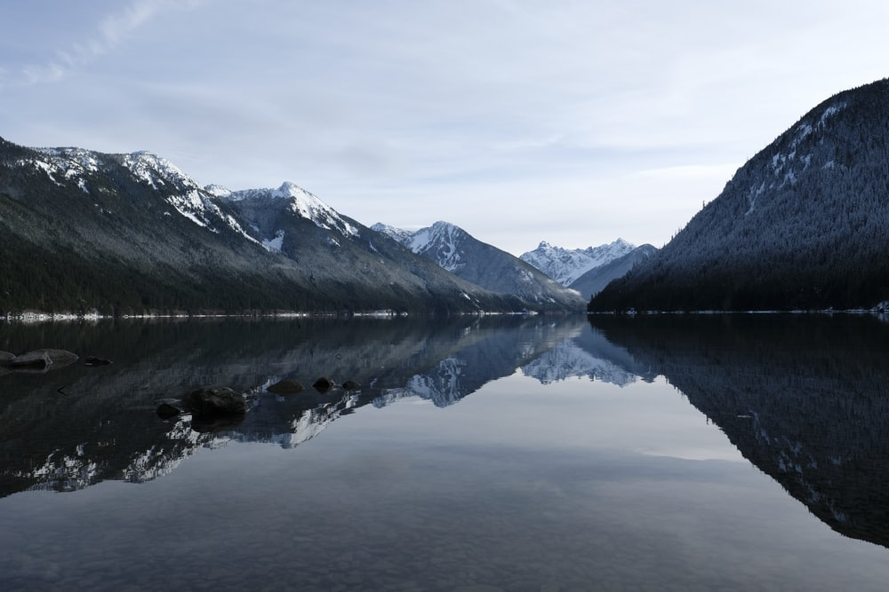landscape photo of black and white mountains near body of water during daytime