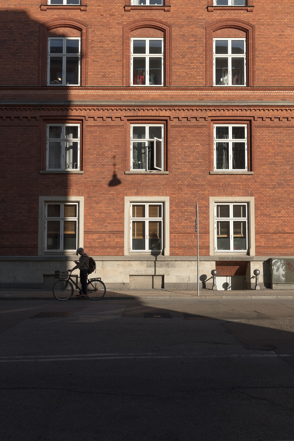 person riding road bike beside brown brick building during daytime